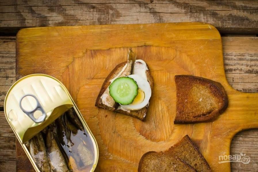 Поверх гренок с майонезом положите шпроты из банки. Затем выложите на хлеб по кружочку вареного яйца и свежего огурца. Украсьте гренки зеленью и подавайте к столу.