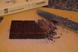 """1. Включите духовку нагреваться на 180 градусов. Две круглые формы, диаметром чуть более 20 см, застелите пергаментом или смажьте маслом (растительным или сливочным). Немного шоколада (50 г) оставьте для украшения, можно его """"побрить"""" ножом и оставить в холодильнике. Остальное поломайте на кубики и выложите в сотейник."""