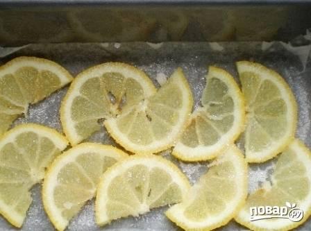 Форму для выпечки обязательно застилаем пергаментной бумагой. Выкладываем ломтики лимона и посыпаем их сахаром.