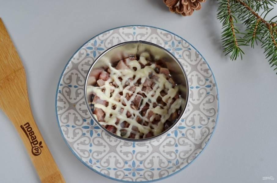 Возьмите тарелочку, поставьте первое кольцо. Первый слой салата — селедка, майонезная сеточка.