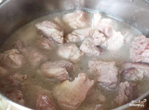 После этого переложите свинину в кастрюлю, влейте воду, чтобы она покрывала мясо. Поставьте на средний огонь.