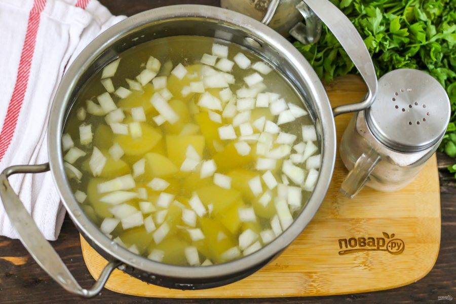Овощи очистите от кожуры и промойте в воде. Нарежьте картофель средними кубиками, а лук — мелкими и выложите обе нарезки в кастрюлю или казан. Залейте горячей водой и отварите примерно 10-12 минут с момента закипания жидкости. Удалите пену, если она образовалась.
