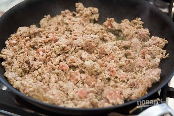1.Отварите макароны в подсоленной воде до готовности, затем откиньте на сито и промойте. В сковороде разогрейте столовую ложку масла, выложите фарш и разомните его, посолите.