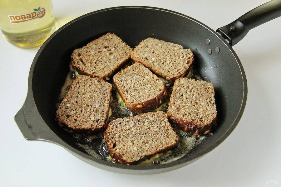 Подготовленные бутерброды выложите начинкой вниз на хорошо разогретую сковороду с растительным маслом.