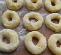 Нашу нежную консистенцию разрезаем на небольшие кусочки. Из них мы делаем колбаски и один конец закрепляем с другим, получаются бублики. Советую делать колбаски тонкими, чтобы они хорошо пропекались, а внутри не были сырыми. Пончики готовы к жарке.