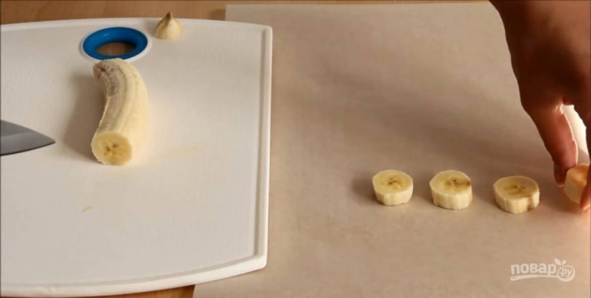Пока тает шоколад, банан очистите  от кожуры, нарежьте на шайбочки и выкладывайте на пергамент.