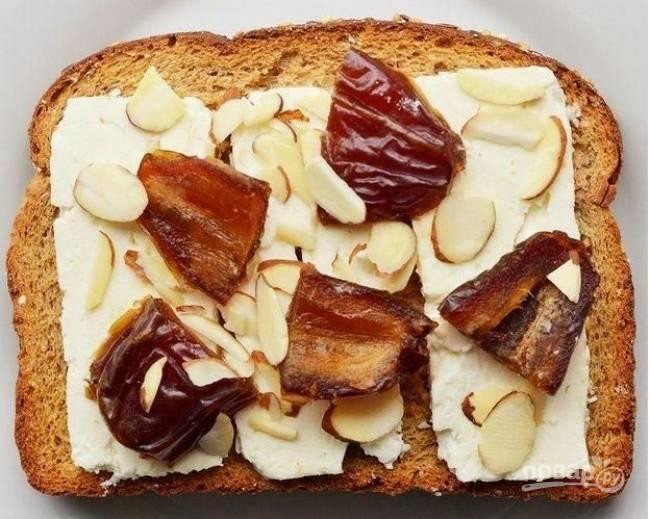 На хлеб выложите сыр, затем разрезанный финик и миндаль.