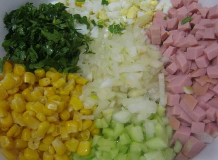 В салатницу складываем кукурузу (без жидкости), порезанные яйца, огурец, колбасу, а также измельченную зелень и лук. Добавляем соль по вкусу.