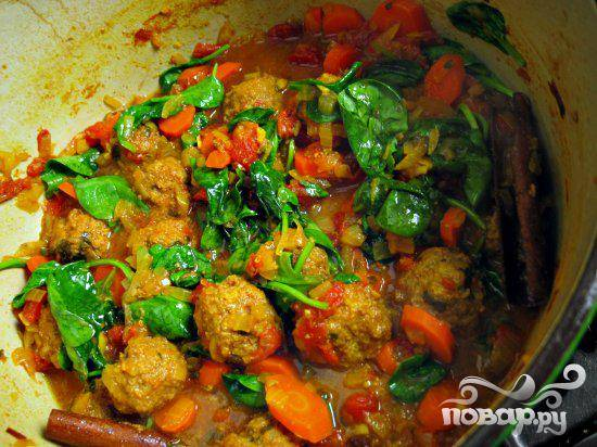 3. Приготовить овощное рагу. Нарезать лук, кинзу, пропустить чеснок через пресс. Морковь нарезать по диагонали тонкими ломтиками. Нагреть масло в большой кастрюле на среднем огне. Добавить лук, жарить около 15 минут. Добавить чеснок, корицу, куркуму, испанскую приправу и перемешивать в течение 2 минут. Добавить мясной бульон, помидоры с соком и изюм. Разогреть духовку до 175 градусов. Перемешать рагу с морковью. Осторожно добавить фрикадельки в рагу. Посыпать 1/4 стакана кинзы. Поместить кастрюлю в духовку и запекать  фрикадельки с рагу до готовности, пока морковь не станет мягкой, примерно 35 минут.