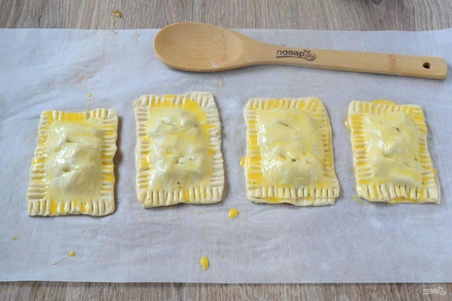 Края смажьте взбитым яйцом, накройте сверху прямоугольниками теста, вилкой закрепите края. Благодаря тому, что мы смазывали края яйцом, тесто хорошо сцепится. Сверху пирожки также смажьте взбитым яйцом, сделайте небольшие надрезы. Переложите пирожки на противень, застеленный пергаментом, и запекайте в духовке 20-25 минут при температуре 180 градусов. Запекать нужно до золотистого цвета.