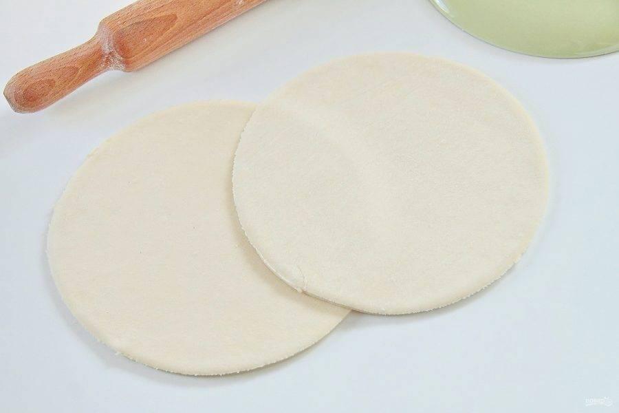4. Как правило в упаковке идет два пласта теста. Каждый необходимо раскатать на присыпанной мукой поверхности и приложив любую подходящую по размеру тарелку, вырезать при помощи ножа круги, обрезав углы.