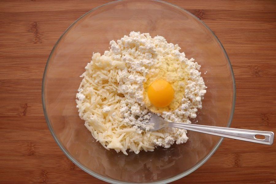 Для того чтобы приготовить начинку, натрите сыр на крупной терке, добавьте к нему творог и одно яйцо, перемешайте.