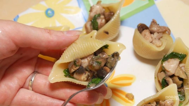 Готовые макароны промойте и остудите. Перемешайте их с небольшим количеством сливочного масла. В ракушки разложите начинку из первого шага.