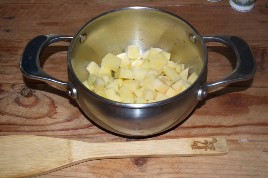 В кастрюлю положите картофель. Залейте водой и поставьте вариться.