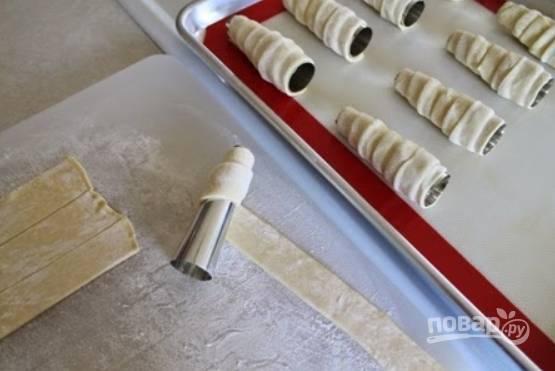 5.Возьмите железные конусы или трубочки, оберните вокруг каждой (предварительно смажьте маслом) полоску слоеного теста, формируя трубочку.