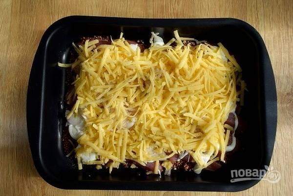 Сверху полейте сметаной, посыпьте сыром,  натертым на крупной терке. Добавьте соленую горячую воду.