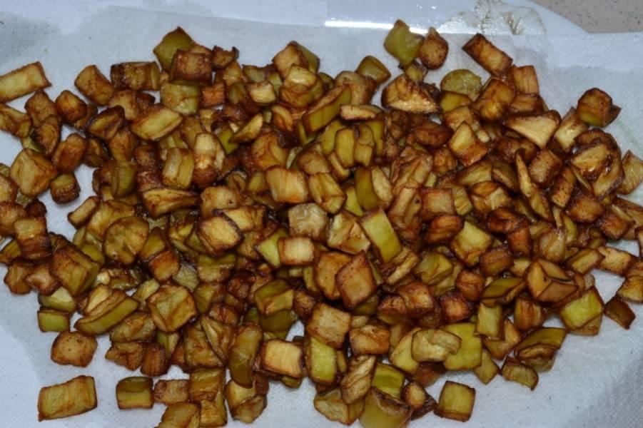 1. Баклажаны нарежем мелкими кубиками. Растительное масло наливаем в кастрюльку и доводим до кипения. Обжариваем овощи до золотистого цвета. Затем выкладываем баклажаны на салфетку, чтоб лишний жир ушел.