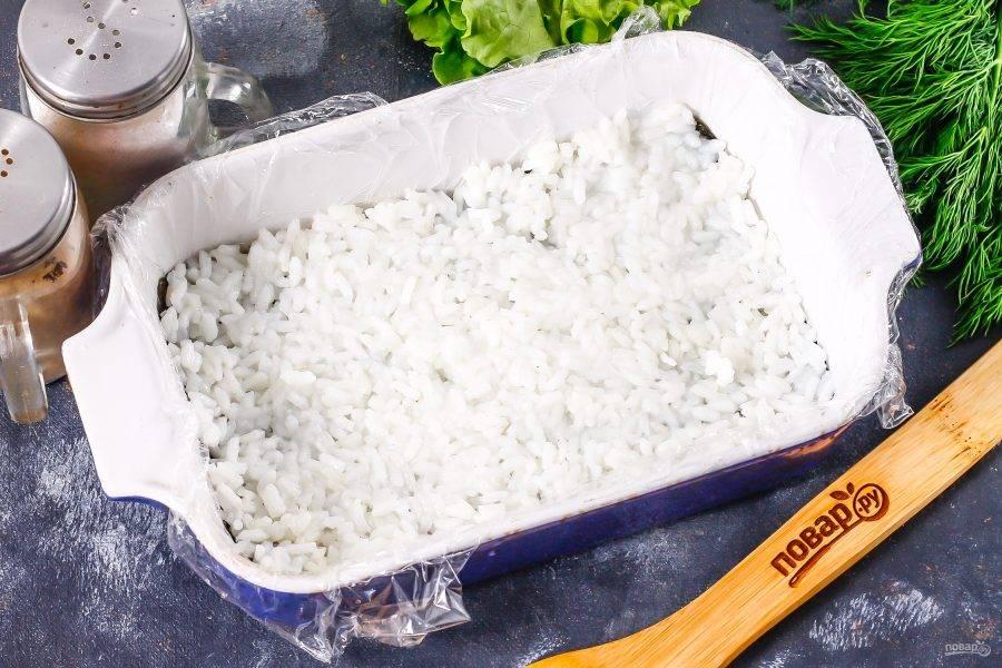 Распределите по нори рис тонким слоем, смачивая руки в воде.