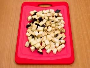 Нарежьте кубиками баклажаны.