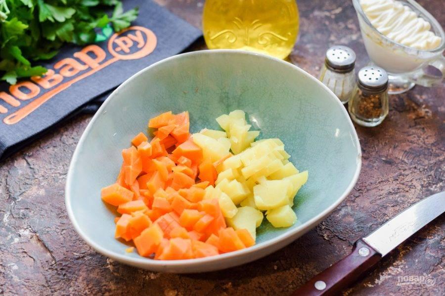 Отварной картофель и морковь очистите, нарежьте кубиками и переложите в салатник.