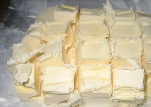 Из холодильника достаньте сливочное масло. Дайте ему постоять, чтобы оно стало мягким. Затем разрежьте его на кубики и добавьте в горячее молоко.