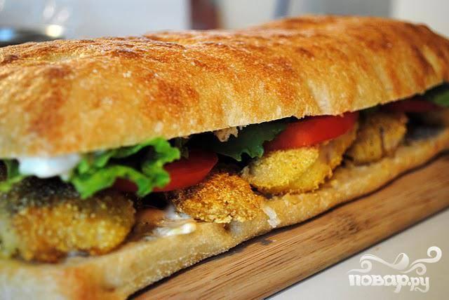 5. Затем положить слой рыбы, помидоры, салат, накрыть сверху второй половинкой хлеба, нарезать на порции и сразу подавать.