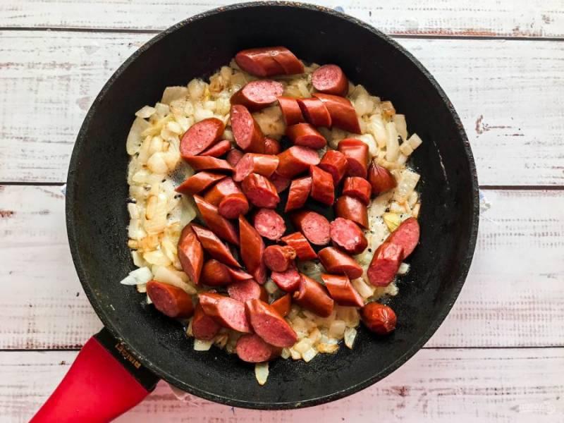 Добавьте нарезанные жареные колбаски и обжарьте их в течение 5-7 минут.