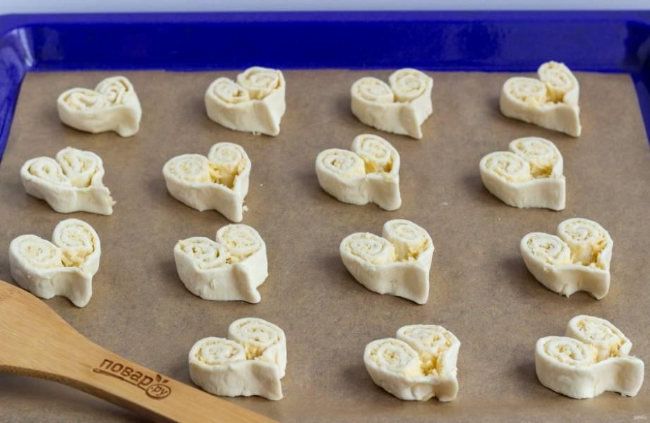 Нарезайте слойки-печенье порционно, толщиной по 1 см, и выкладывайте на противень с пекарской бумагой, защипывая снизу и формируя сердечко. Раскладывайте на небольшом расстоянии друг от друга. Со второй частью теста и сыра сделайте то же самое. Из двух пластин теста у меня получилось 30 слоечек.