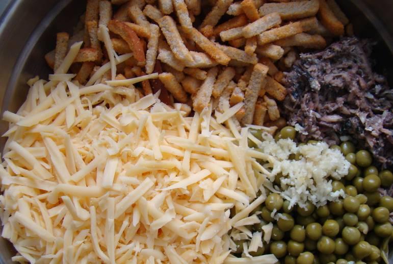 В глубокой миске соединяем: шпроты, тертый сыр, зеленый горошек, пропущенный через пресс чеснок и сухарики.