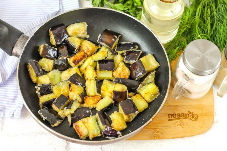 Прогрейте сковороду с растительным маслом и высыпьте в него баклажанную нарезку. Обязательно выкладывайте только в раскаленное масло, чтобы панировка сразу обжаривалась. Убавьте нагрев до среднего и жарьте нарезку примерно 3-4 минуты, время от времени перемешивая.