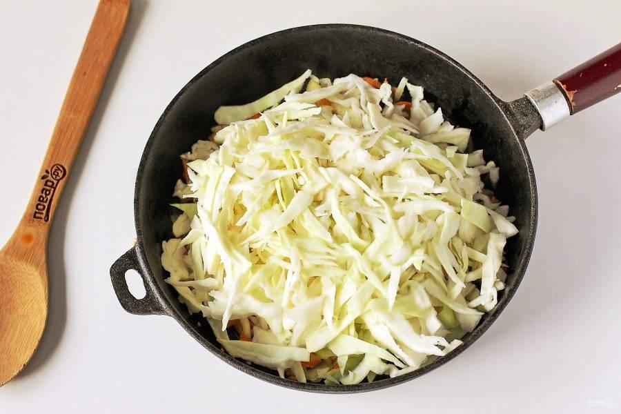 Нашинкуйте капусту и добавьте к луку и моркови.