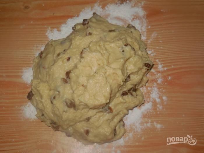 Пока тесто жидкое, добавьте изюм и хорошо вымешайте тесто руками.