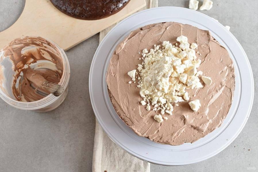 Выложите сверху второй корж, намажьте вторую половину сметанного крема и посыпьте разломанными меренгами.