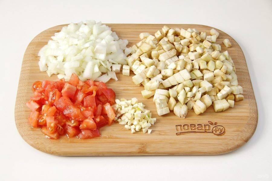 Для начинки нарежьте кубиками лук, баклажан и чеснок. У помидора удалите шкурку, подержав его перед этим в кипятке около минуты и так же нарежьте небольшими кубиками.