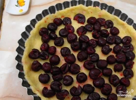 Возьмите форму для выпечки, распределите по ней тесто. Потом разложите на тесто ягоды, залейте все сливочной массой.