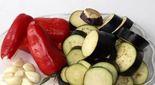 2. Нарежьте все овощи. Баклажаны следует нарезать кольцами, толщина которых должна составлять до 0,7мм. Все остальные овощи измельчите мелко. Помидоры нужно пропустить через мясорукбу.