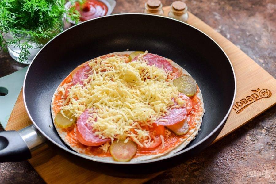 Засыпьте всю заготовку сыром, прикройте сковороду крышкой и готовьте пиццу на маленьком огне 4-5 минут. Спустя время можно подавать пиццу к столу.