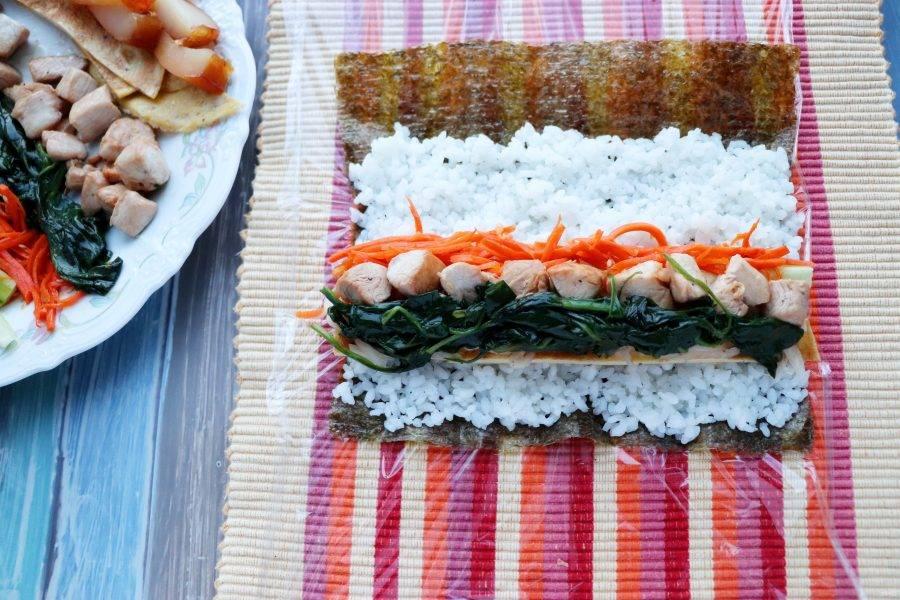 На лист нори выложите рис, удобно это делать слегка влажными руками. На рис положите омлет, морковь, дайкон, огурец, шпинат, кусочки мяса. Аккуратно сверните плотный ролл. В следующий ролл вместо мяса положите рыбу. Третий ролл приготовьте без мяса и рыбы, он будет вегетарианским.