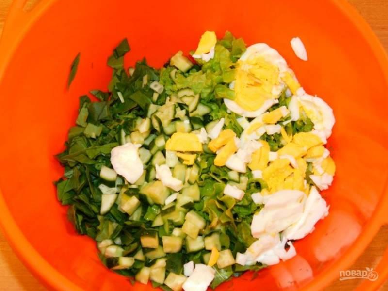 Добавьте нарезанные листья салата и яйца. Заправьте салат сметаной и хорошо перемешайте.