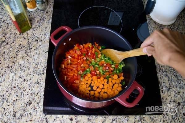 7. Разогрейте в кастрюле растительное масло. Выложите зеленый лук и обжарьте 3-4 минуты. После добавьте сладкий перец, морковь.