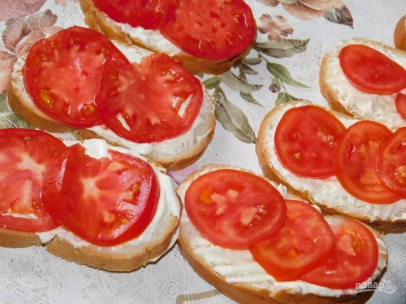 Ломтики батона смажьте сырной пастой, а сверху разложите помидоры, нарезанные кружочками.