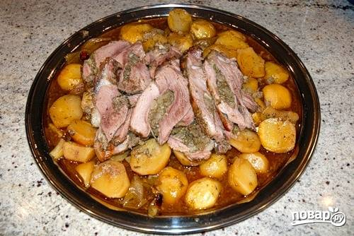 Подавайте запеченную баранью ногу вместе с картофелем, порезав на куски.