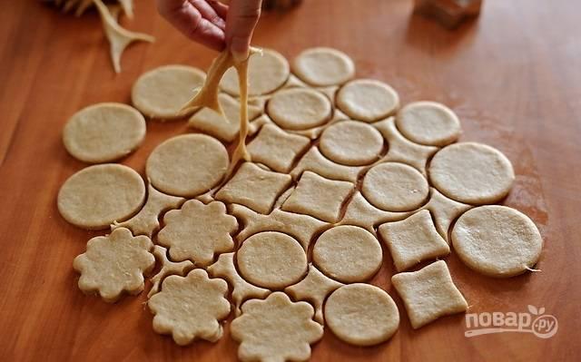 2.Специальными формами или стаканом вырезаю печенье, затем аккуратно снимаю остатки теста. Обрезки собираю вместе и снова раскатываю, затем опять формочками вырезаю печенье.