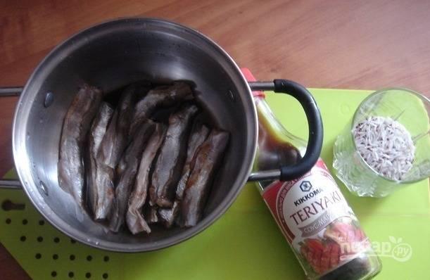 Мойву подготовьте, удалив потроха, голову и хвост. Затем рыбу залейте соевым соусом. Оставьте её мариноваться на 30 минут.