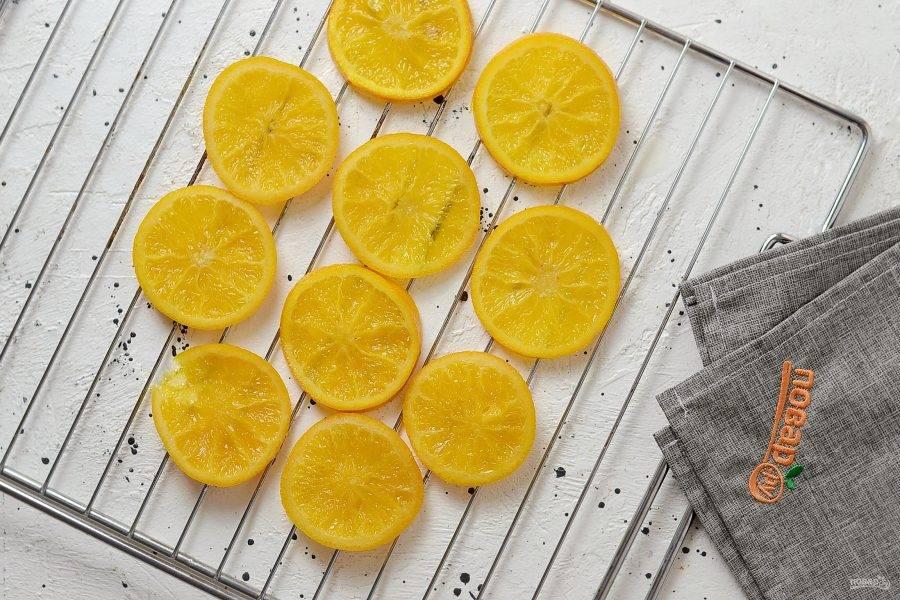 Затем выложите апельсины на решетку, дайте стечь сиропу. Затем подсушите в духовке примерно 30-45 минут при температуре 130 градусов.