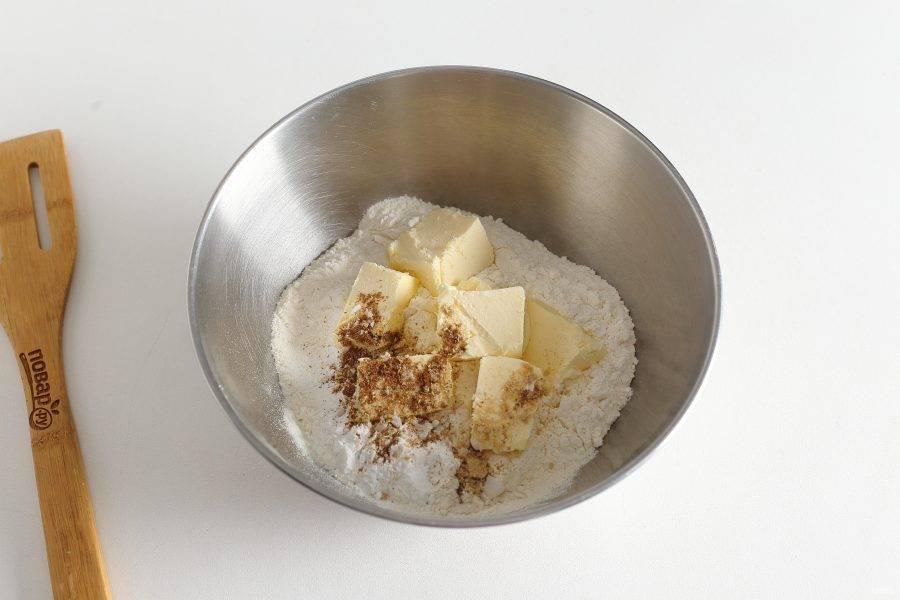 В глубокой миске соедините муку, нарезанное кубиками сливочное масло, разрыхлитель и специи по вкусу.
