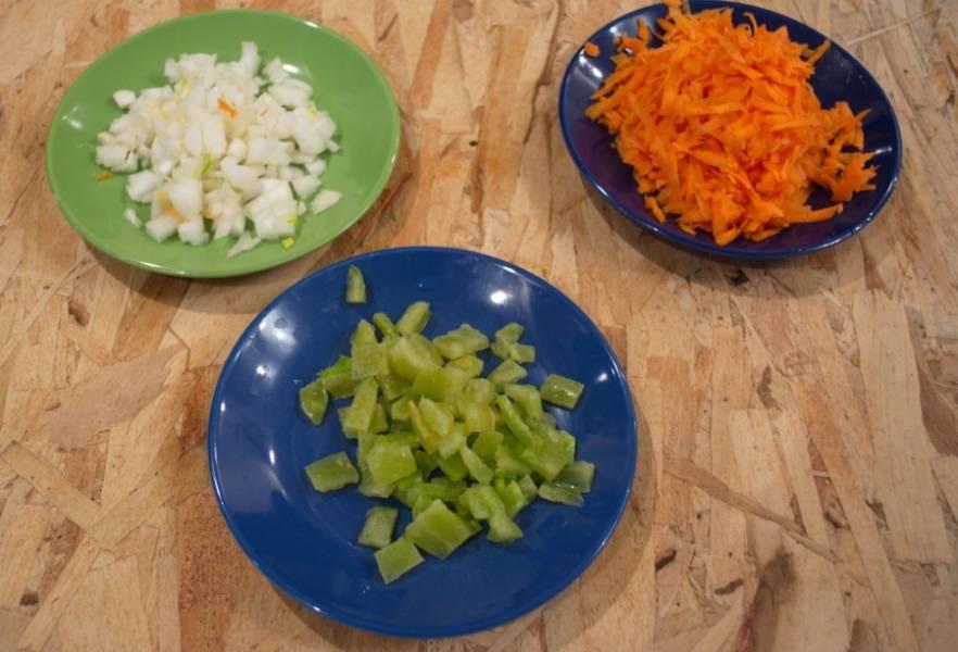 Через 5 минут после закипания воды с картофелем, добавляем в бульон капусту и варим.  Теперь нарезаем овощи для зажарки: лук, морковь, болгарский перец.