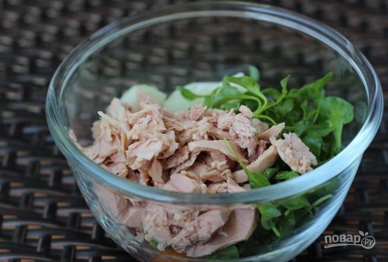 Выложите подготовленные овощи в салатник. Затем откройте банку консервированного тунца, слейте лишнюю жидкость и помните рыбу вилкой, если это потребуется. Выложите рыбу к овощам, добавьте к ней листья салата.