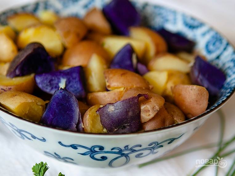 Отваренный картофель нарежем половинками или четвертинками, пусть пока остынет. Тем временем промоем и измельчим лук (оба вида) и другую зелень.