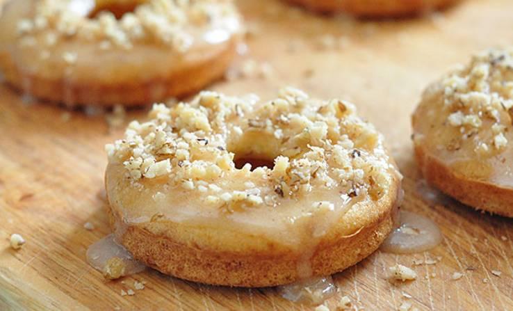 Выпекайте пончики в духовке 30 минут, температура 180 градусов. Тем временем приготовьте глазурь: для этого смешайте сахарную пудру с корицей, добавьте необходимое к-во молока. Готовые пончики слегка остудите, полейте глазурью и посыпьте орешками.